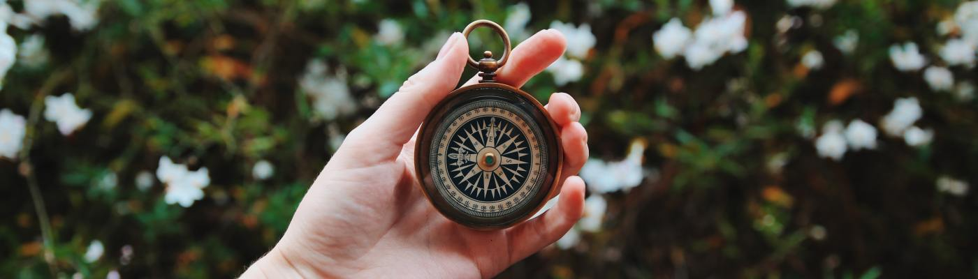 Photo of a hand holding a compass for the poem The Traveler's Quest