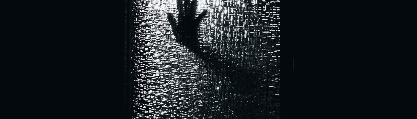 Silhouette of hand against distorted glass with geometric shapes. black and white color.